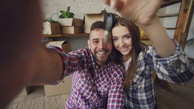Point of view shot of happy couple taking selfie with house keys after purchasing new apartment. Young people are