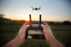 Point of view shot of man holding remote controller with his hands and taking aerial photo video. Quadcopter is flying stock photography
