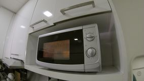 Point of view shot of a man using a microwave oven in a kitchen