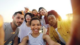 Point of view shot of African American girl holding camera and taking selfie with happy friends at party on roof. Men. Point of view shot of pretty African stock video footage