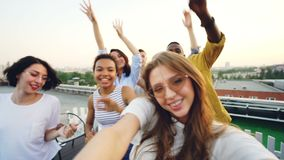 Point of view shot of pretty young woman recording video of rooftop party with her friends dancing and looking at camera