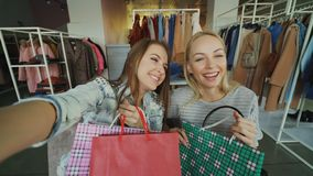 Point of view shot of two attractive careless girls making selfie with paper bags in women`s clothes shop. Friends are. Point of view shot of two attractive stock video footage