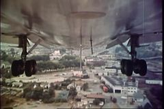 Point of view shot of undercarriage of an airplane flying over city stock footage