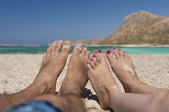 At the Beach. Point of View Showing Couples Feet Lying at Sandy Beach Royalty Free Stock Photos