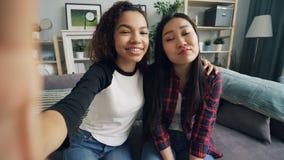 Point of View tiró de las mujeres jovenes hermosas que tomaban el selfie en casa que miraba la pantalla, sonriendo y presentando  almacen de video