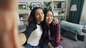 Point of View tiró de las señoras jovenes atractivas afroamericano y selfie que tomaba asiático en casa entonces que presentaban  almacen de metraje de vídeo