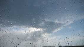 Point of view through the windshield of car with raindrops to the cloudy sky. Close up of water droplets on windowpane stock video