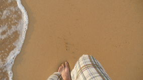 Point of view of young man stepping at the golden sand at sea beach. Male legs walking near ocean. Bare foot of guy stock footage