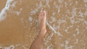 Point of view of young man stepping at the golden sand at sea beach. Male legs walking near ocean. Bare foot of guy