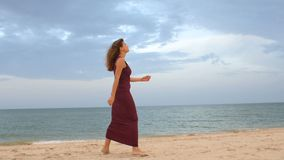Point of view of young woman stepping at the golden sand at sea beach. Female legs walking near ocean. Bare foot of girl going on. Sandy shore with waves stock video