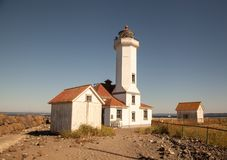 Point Wilson Lighhouse buildings. On the edge of landsend the Point Wilson lighthouse is an historical structure near Port Townsend Washington. Gleaming against Stock Photo