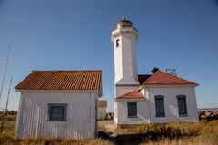West Coast old Lighthouse. On the edge of landsend the Point Wilson lighthouse is an historical structure near Port Townsend Washington. Gleaming against a Royalty Free Stock Photography