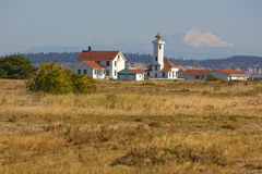 Point Wilson Lighthouse at Fort Worden. State Park, Port Townsend, Washington, with Mount Baker in the background royalty free stock photography