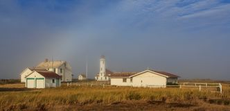 Lighthouse with gleaming spotlight of sunlight and light misty feel. stock image