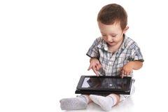 Pointage d'enfant en bas âge de bébé confus à un comprimé numérique Photographie stock