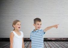 pointage d'enfants étonné avec le fond vide de pièce Images stock