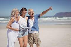 Pointage heureux d'homme supérieur parti tout en se tenant avec la famille à la plage photo libre de droits