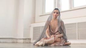 Сфокусированная и спокойная балерина кладя на ботинки pointe сидя на сером каменном поле акции видеоматериалы