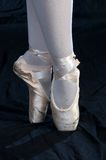 On Pointe. A view af a ballerina's feet as she stands on Pointe, shoes worn from practice stock photo