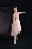 On Pointe. A ballerina posed on Pointe in peach colored dress stock images