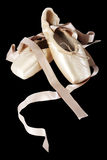 Pointe ballet shoes on black background. One pair of pointe shoes on black bacground Royalty Free Stock Photo