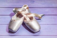 Pointe cal?a sapatas da dan?a do bailado com uma curva das fitas dobradas belamente em um fundo de madeira foto de stock royalty free