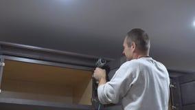 Pointe de charpentier utilisant l'arme à feu de clou pour couronner le moulage sur des buffets encadrant l'équilibre banque de vidéos