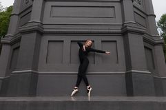 Pointe del en de la bailarina de puntillas cerca de la pared negra Imágenes de archivo libres de regalías