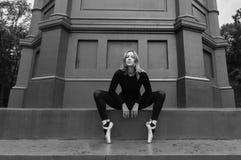 Pointe dell'en della ballerina vicino alla parete nera Fotografie Stock