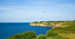 Pointe du Hoc cliffs in clear sky and calm sea France royalty free stock images