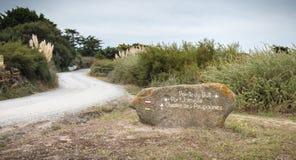 Pointe du But, Joinville-Hafen, Chemin DES Poupounes malte auf einem großen Stein, der einen langen Trekkingsweg anzeigt lizenzfreies stockbild