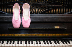 Pointe and piano. Pink pointe on the black old piano royalty free stock image