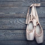 Pointe shoes ballet dance shoes with a bow of ribbons hang on a nail on a wooden background