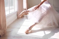 Pointe shoes on the feet of a ballerina. Pointe shoes on the feet of a ballerina on the background of a sunny window in the room royalty free stock photo
