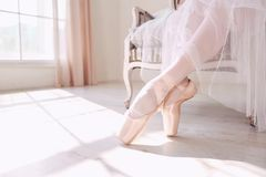 Pointe shoes on the feet of a ballerina. Pointe shoes on the feet of a ballerina on the background of a sunny window in the room stock images