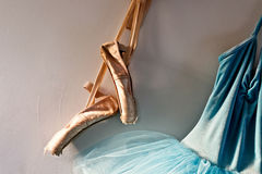 Pointe shoes and tutu. A blue velvet romantic tutu is hanging on a wall beside a worn pair of ballet pointe shoes, lit only by sunlight through window Royalty Free Stock Photo