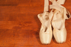 Pointe shoes on a wooden background with copyspace Stock Photos