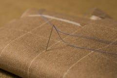 Pointeau et amorçage sur le fond de tissu Photographie stock libre de droits