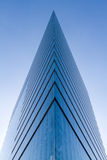 Pointed modern building. Low angle view of glass windows on corner of modern, pointed skyscraper building with blue sky background royalty free stock photos