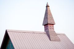 A pointed roof. Wooden tower with a pointed octagonal roof against a blue sky stock photography