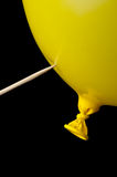 A pointed stick ready to pop a yellow balloon. On black royalty free stock photo