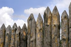 Pointed stockade, a fence made of pine logs. Against the sky Stock Photography