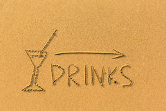 Pointer arrow, glass and the words Drinks drawn on the sand beach. Happy. Royalty Free Stock Image