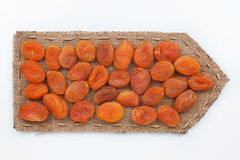 Pointer of  burlap with dried apricots Royalty Free Stock Photo