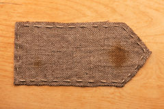 Pointer of burlap, lies on a background of wood Stock Photography