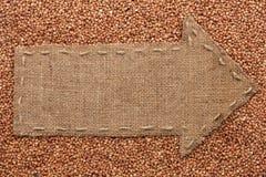 Pointer of  burlap lies on  buckwheat  grain Royalty Free Stock Image