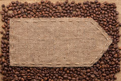 Pointer of burlap lying on a coffee beans background. With place for your text Royalty Free Stock Images