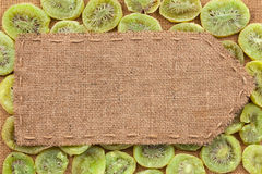 Pointer of burlap lying on a dry kiwis background. With place for your text stock photos