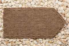 Pointer of burlap lying on a pumpkin seeds background Stock Photos