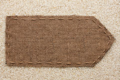 Pointer of burlap lying on a rice background Stock Photo